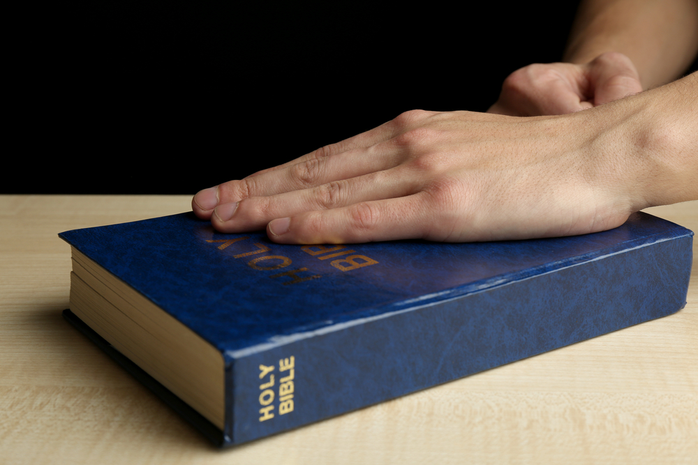 Image of hand on Bible